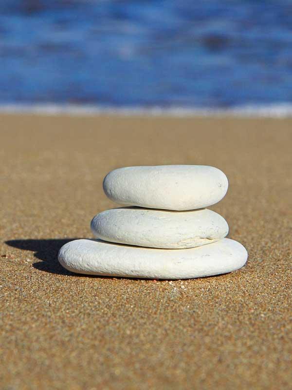Aufeinandergetürmte, flache Steine an einem Sandstrand